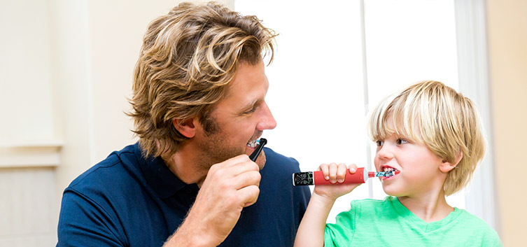 parent and kid with electric toothbrush